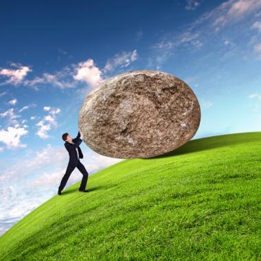 man pushing rock